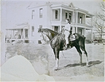 Need ID for young rider on horse. Perhaps use the house as a guide. Also note the saddle is western. Who rode quarter breeds?
