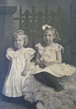 Two young girls, probably sisters in a portrait seating